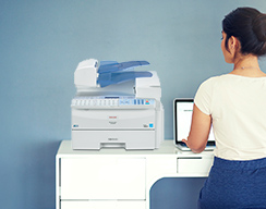 Ricoh fax machine. Woman sitting at desk.