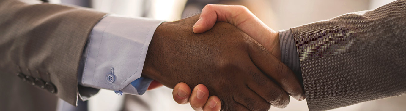 Closeup of two men shaking hands wearing suits.