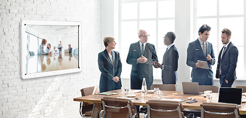 Group of co-workers in conference room with interactive whiteboard in background