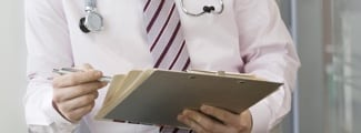Doctor holding a clipboard close up