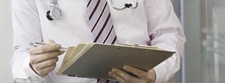 Close up of doctor holding clipboard