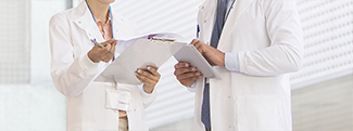 Bottom half of doctors next to each other with clipboards