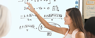 Girl using interactive whiteboard solving math problem in classroom