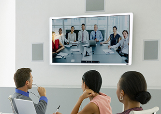 people in a meeting room on a video conference with another meeting room full of people