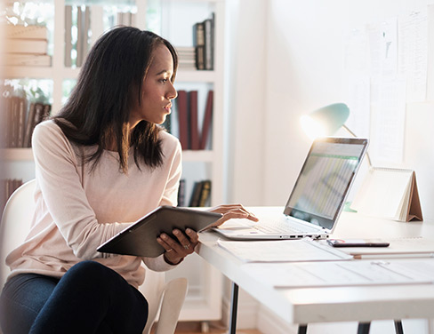 business woman on device and laptop