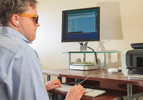 visually impaired man using assistive technology to view computer files