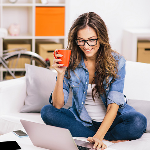 Student working at home on laptop with coffee