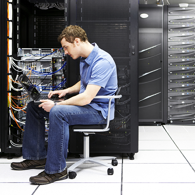 man sitting working in server room