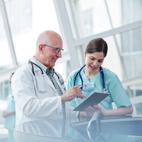 doctor and nurse talking together and using digital tablet