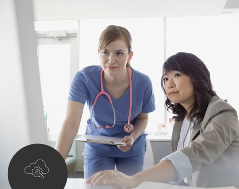Woman working on computer with doctor