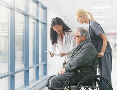 doctors with a patient in a wheelchair and showing patient digital tablet
