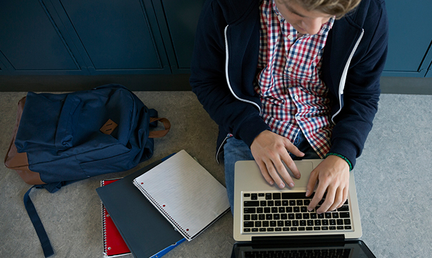 Student up against lockers on laptop