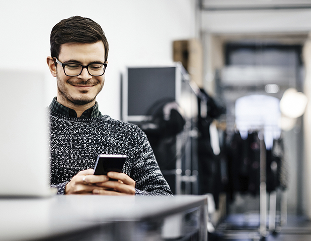 man at office desk checking on phone