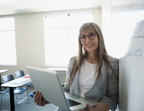Female teacher holding laptop and smiling