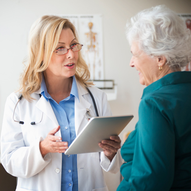 older woman and doctor talking in room