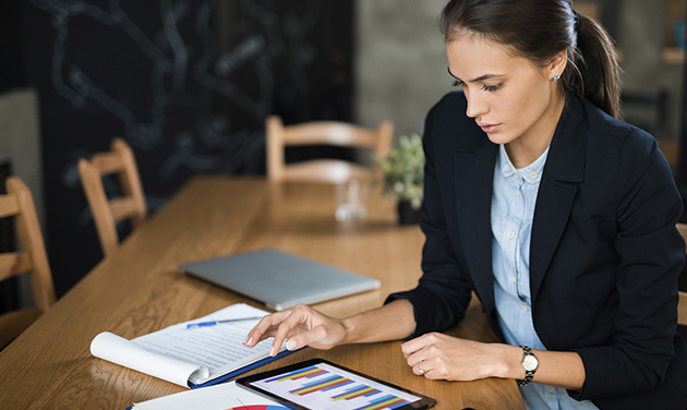 Woman at desk with tablet showing data report
