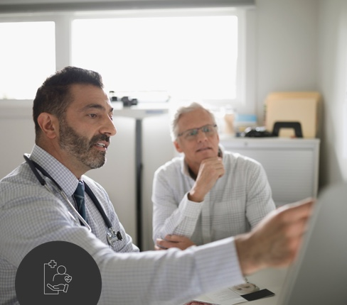 Male doctor with patient pointing on tablet