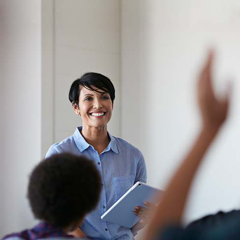 Smiling professor in classroom with hand raises