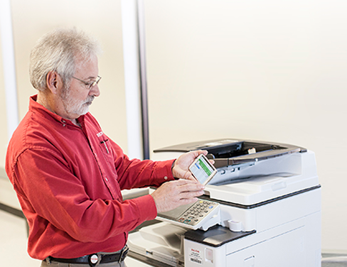 ricoh employee at printer interacting