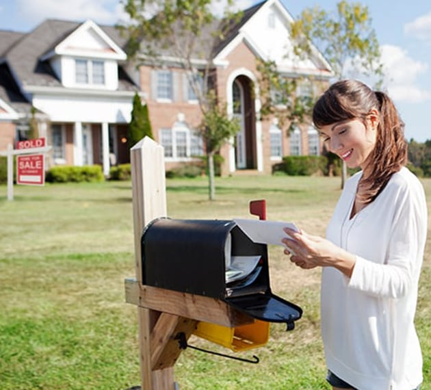 Woman grabbing mail at mailbox with sold house in background