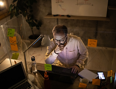 man on computer surrounded by post-it notes