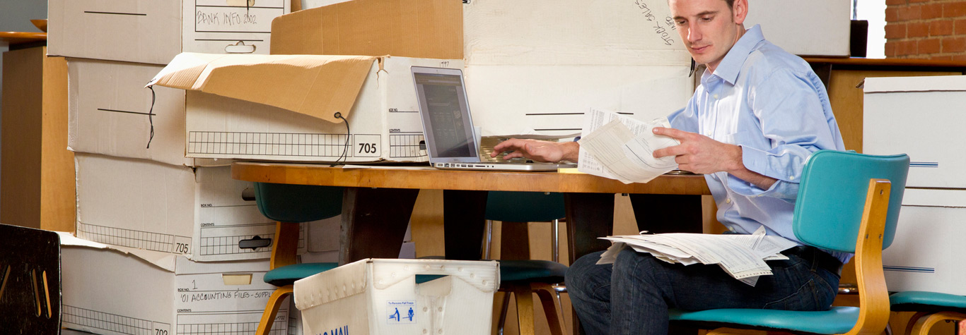 man in back office sorting through papers and mail