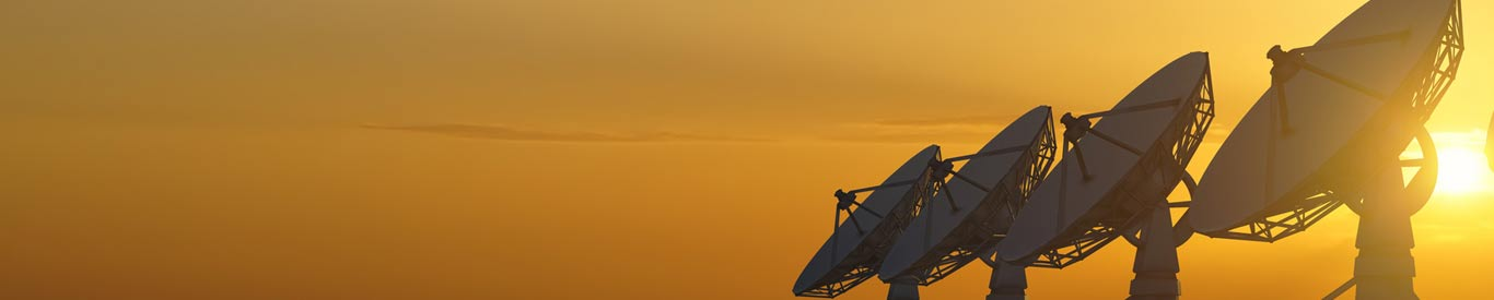 satellite dishes in a line at sunset