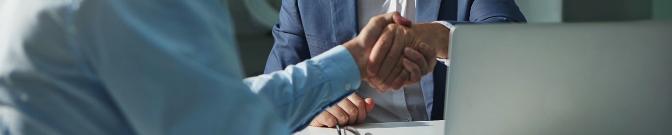 Shot of two businessmen shaking hands in an office.