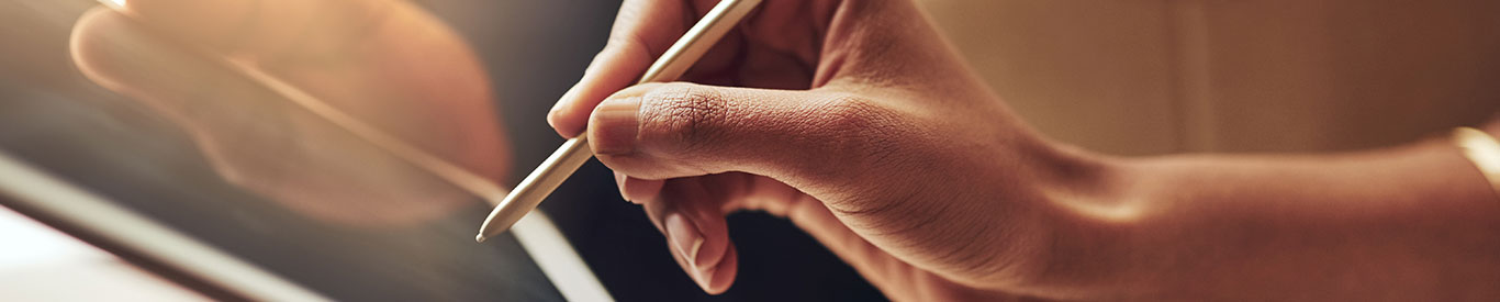 hand using a stylus to sign a tablet for receiving a package