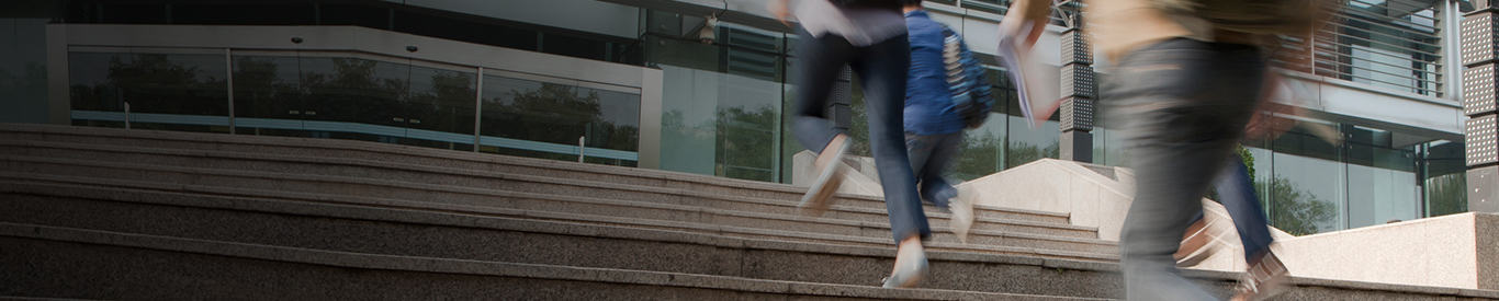 Students running to class up stairs on campus
