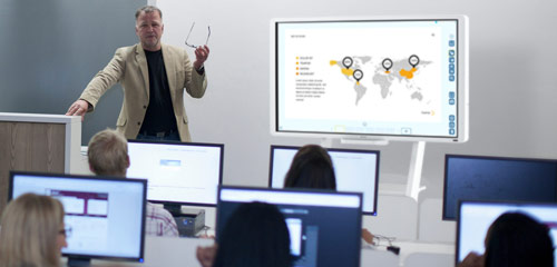 professor teaching with interactive whiteboard. A map graphic is displayed on the whiteboard