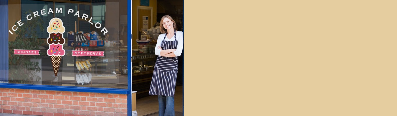 Woman in front of bakery store front with decals on window