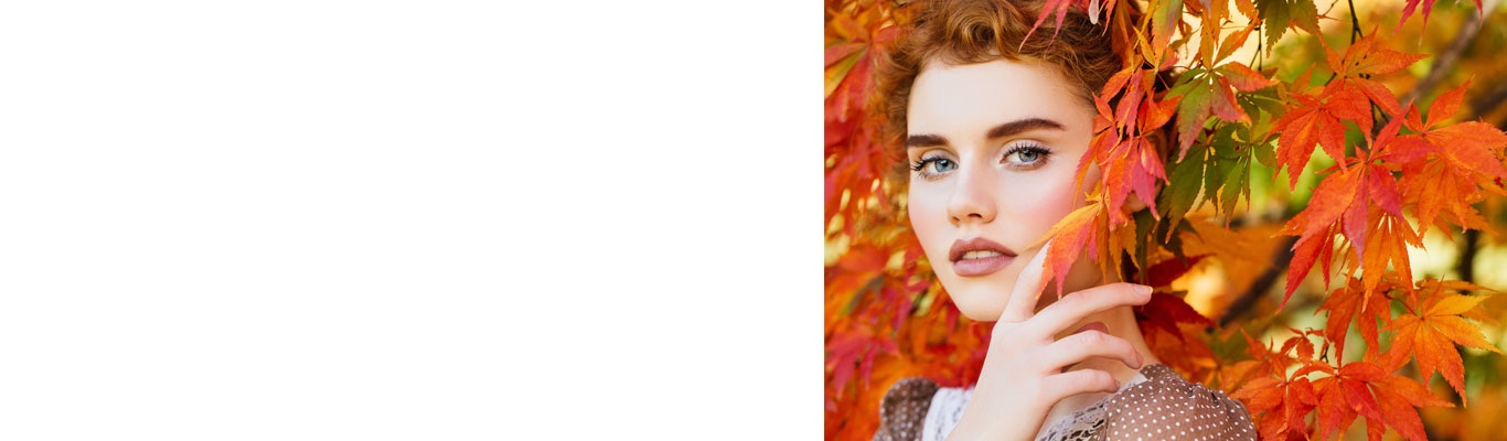 Woman with red hair in fall leaves tree