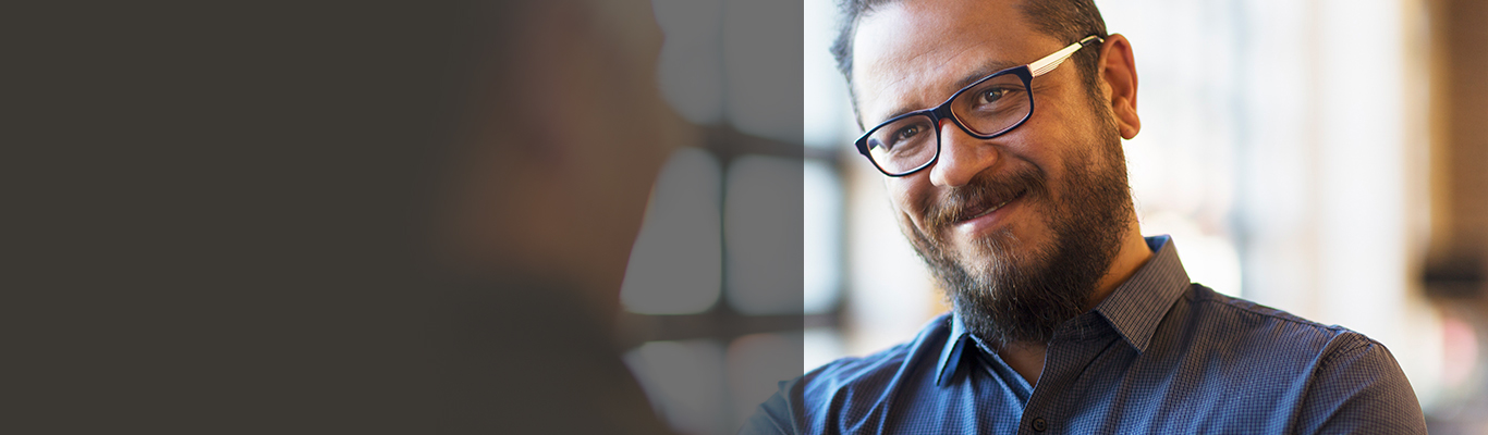 consulting man with glasses talking to someone and smiling