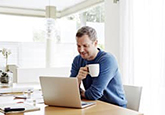 man at computer with mug