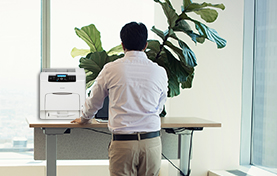 Man standing at desk with MFP printer
