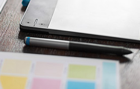 Photo of a tablet, pen, and color swatches on a table.