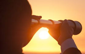 person looking through telescope at sunset
