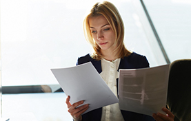 Professional woman in meeting room looking over paperwork
