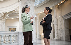 two women having a discussion in a government building