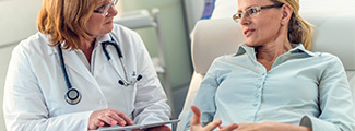 Woman doctor showing patient laying down in polo information on tablet