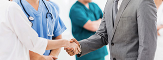 Doctor shaking hands with a man in a suit