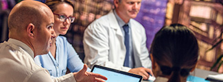 Group of doctors conversing around a computer screen