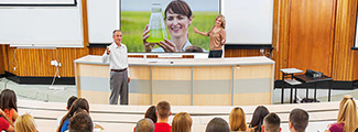 Photo of students watching a teacher teach on an interactive flat panel display.