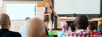 teacher in front of students in lecture hall with interactive whiteboard