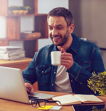Photo of a man with coffee and his computer.