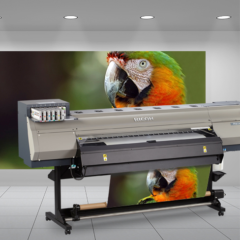 Man with tablet in front of wide format Ricoh printer