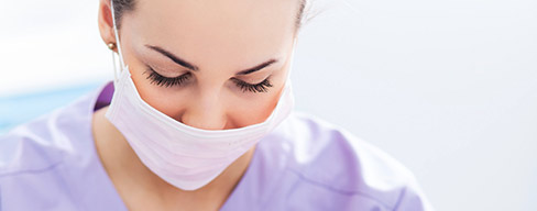 Female dentist wearing face mask.
