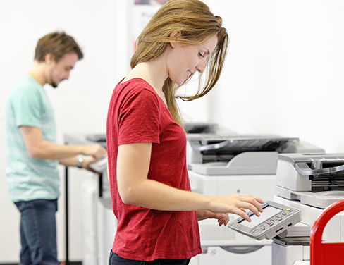 Photo of a girl in a red shirt working at a printer.