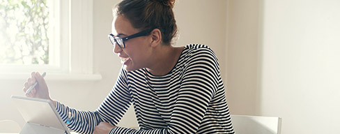 Photo of a girl in a striped shirt and glasses, smiling and working on a tablet.